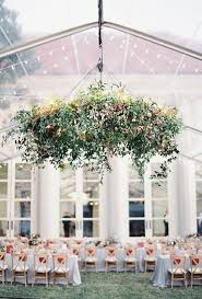 wedding reception chandelier covered in greenery