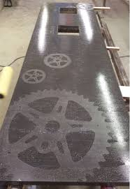 deep gray integrally colored concrete countertop with embedded metal gears
