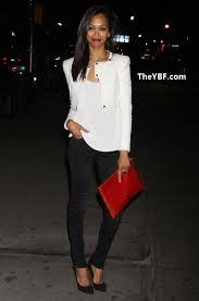 zoe saldana in a simple white top black skinny jeans black pumps a white leather jacket and a red bag