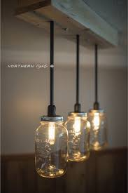 similar design clear glass jar pendant light hanged on wooden ceiling backing warm long bulb