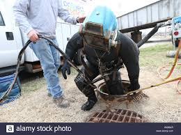 Diver Dustin Arnold is helped out of a sewer manhole after installing a  large plug into an inlet to prevent flooding from the Mississippi River in  St. Louis on March 28, 2019.