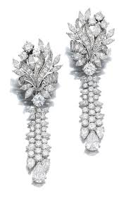 pair of diamond pendent earrings each earring featuring a surmount of fl design suspending a tel motif set with marquise pear shaped