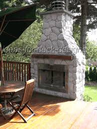 stone covered outdoor fireplace for a backyard deck