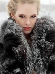 a beautiful blonde woman models a full and soft full length fur coat in boston