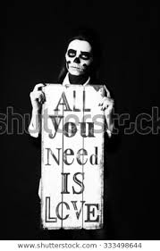 young beautiful woman with skeleton face art makeup holding all you need is love