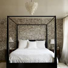 This sleek ebony modern four poster bed is juxtaposed against a rustic  brick wall. The interest level was heightened by adding another layer of  contrast, ...