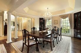 crystal chandelier dining room lighting fixtures for low ceilings over a dark wooden table and wooden chairs on an oriental rug