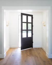 black front door with glass and brass sconces