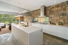 stone wall connects the kitchen with the pool deck outside design rodrigues coat architects