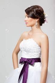 スタジオで髪型と白の結婚式で Orhid と美しいブルネットの花嫁の肖像画がドレスアップします