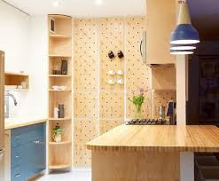 this small kitchen features a pegboard wall and open shelving for extra storage