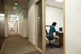 View Down A Hallway With An Asian Woman In Meeting Office