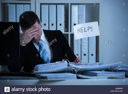 Stressed Accountant Holding Help Sign At Desk While Working Late In