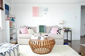 big modern sofa with fancy pillows and round table on rug in a bright small living
