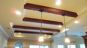 a kitchen s tray ceiling lined with beams with both recessed and hanging lights