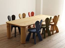 larger unfinished wood table with unique and fun colored chairs