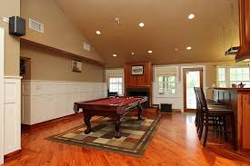 diagonal wood floor installation under large multi color rug and small pool table also cream