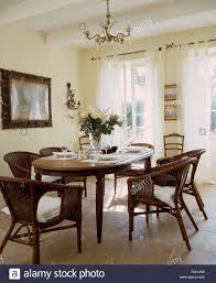 country dining room set. Wicker Chairs At Oval Antique Table Set For Lunch In White Country Dining Room With Voile Drapes And Stone Tiled Floor G