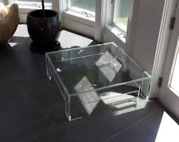 modern square clear acrylic coffee table with shelf in living room with high window and black vinyl floor tiles ideas