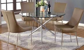 round glass dining table with 4 light brown chairs
