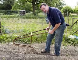 a organic farmer using a high wheel cultivator to make a seed row in a garden