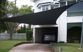 black shade sail over driveway fitted to posts in the garden wall fittings on house