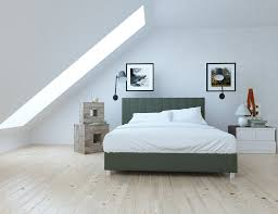 white bedroom with skylight white fitted sheet and pillows on gray bed and wooden flooring