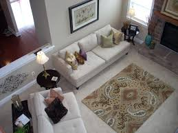view larger area rug on top of carpet