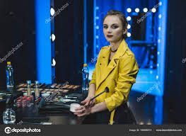 attractive ballerina in yellow leather jacket applying makeup in dressing room photo by natashafedorova