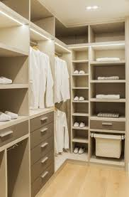 this bedroom closet features bright finishes for a lighter look the cabinet lighting looks good