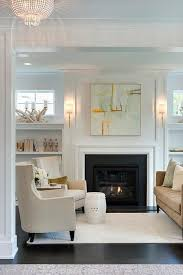 chic living room features a gray and orange abstract art piece illuminated by dauphine sconces hanging over a white sleek fireplace adorned with a black