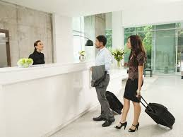 couple arriving at hotel front desk