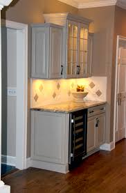 kraft maid cabinetry in a mushroom finish surrounding a custom subway tile pattern granite countertops and a jenn air 24 wine cellar all lit perfectly cabinet lighting custom