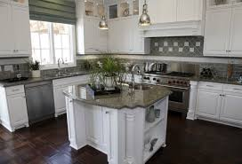 A White Kitchen With Olive Green Tile Backsplash And An Ornate Dark Wood  Floor