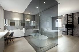 beautiful bathroom with glass wall wood flooring black chair bathtub and white bedroom