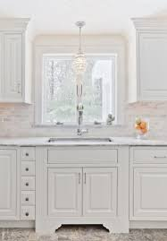 beautiful kitchen with white cabinets white marble countertops mini marble subway tile backsplash and mini crystal chandelier over sink