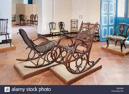 room with antique wooden rocking chairs in the colonial art museum museo del arte colonial in cathedral square havana cuba