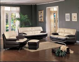 Black and cream leather couch on dark brown wooden floor completed by white  fabric window curtain