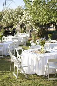 green grass yard and simple white folding chairs also round table under large white table