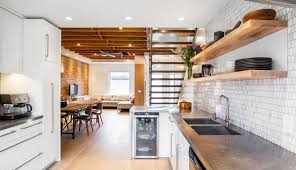 modern basement kitchen exposed wooden beams brick wall dining and living area open shelving