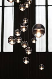14 is an articulated cast glass sphere with a frosted cylindrical void that houses either a low voltage xenon or led lamp individual pendants are visually