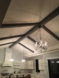 hanging chandeliers from faux beams in a newly remodeled kitchen