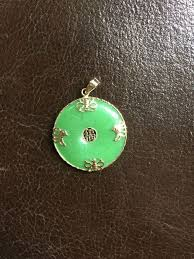 green jade pendant with 14 kt gold decoration and a chinese symbol of good fortune