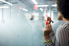 cropped image of businesswoman writing on adhesive notes at glass wall in office stock photo offset