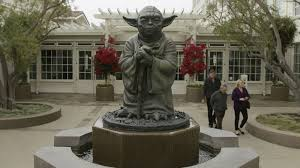 the shadow of greed a brief essay on disney and the business of  people walk past a fountain showing the yoda character from the star wars movies outside of