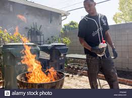 March 17, 2016 - Roberto Smith lights a BBQ grill in Compton Stock Photo -  Alamy