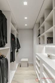 Narrow walk in closet with lots of built in shelves.of course the reality  is that if this was your closet, it wouldn't look like this.
