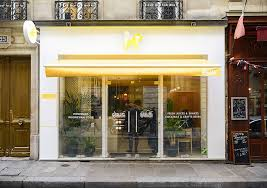 the exterior of the restaurant is bright white with yellow accents and large windows glass doors allow people walking by to easily see into the restaurant
