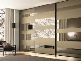 bedroom mirrored glass wardrobe with sliding doors mixed with grey carpet on laminated floor with