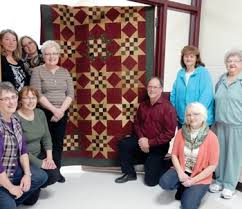 members of cardinal quilters present a dignity quilt to keehr funeral home from left to